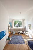Blue rug on floor of child's bedroom with elephant figure and toy car