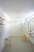 Grosszügiges Bad mit zwei Waschbecken, bunte Klassiker Hocker, vor bodenebenem Duschbereich mit Glastrennscheibe im Hintergrund
