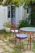 Sitzplatz am Haus mit antiken Gartenstühlen und Gartentisch aus Metall