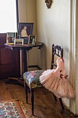 Family photos on antique wooden table in corner next to tutu hung on chair with upholstered seat