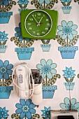 Grüne Wanduhr und altmodischer Mixer an Wand mit geblümter Tapete im 70er Jahre Stil