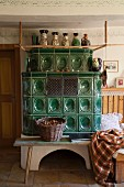 Traditional tiled stove, bench and wicker basket in restored farmhouse