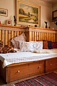 Fitted wooden bench with drawers and embroidered cushions in corner of rustic dining room