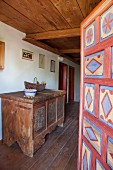 View past open painted door to wooden trunk painted in peasant style in hallway of restored farmhouse