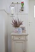 Vintage-style spring arrangement on old bedside cabinet against wainscoting