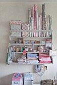 Collection of patterned pastel fabrics and trims on old wall-mounted shelving