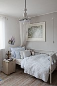 Old metal bed, fan on bedside cabinet, retro pendant lamp and old floorboards with natural patina in teenager's bedroom
