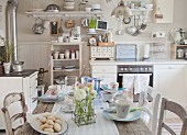 Kitchen-dining room decorated with vintage utensils and ranunculus on set wooden table