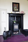 Fireplace accessories on purple-painted wooden floor next to cast iron stove in old fireplace