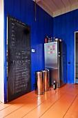 Schiefertafel an Tür, Abfalleimer und Edelstahl Kühlschrankkombination in einer Küche mit blau lackierter Holzwand