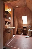 Wood panelling and terracotta floor tiles in modern bathroom in renovated attic