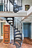 Black, hand-crafted vintage spiral staircase on herringbone terracotta floor in rustic country house with historical ambiance