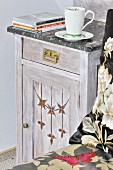 Cup on vintage bedside cabinet with marble top