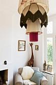 Pendelleuchte mit übereinander gehängten Retro Lampenschirmen, Holzgiraffe in der Ecke hinter Polstersessel mit Schaffell
