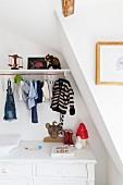 Shelf and child's clothing on clothes rail above white-painted vintage changing cabinet in attic room