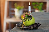 Lit candle stuck in decorated apple