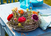 Wicker wreath with multicoloured ranunculus on garden table