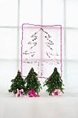 Christmas tree motif made from silver stars on translucent fabric and miniature Christmas trees with pink ribbons
