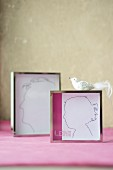 Hand-drawn silhouettes in chrome picture frames and bird ornament