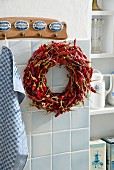 Wreath of dried red chilli peppers hung from wall hooks in kitchen