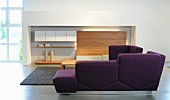 Purple corner sofa in front of wall-mounted cabinet in niche in contemporary lounge area