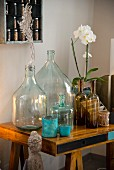 Various glass bottles and potted orchid on desk