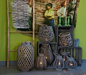 Various lanterns and wooden crates below wall-hanging with picture of children on green wall