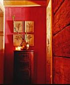 Metallvase mit Bambuszweigen und Windlichter auf zylindrisch geformter Kommode, vor rot getönter Wand