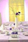 Table set for Easter meal with white crockery and pale lilac tablecloth