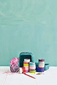 Rolls of washi tape, reels of thread and basket against turquoise wall