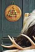 Tablett beklebt mit Weihnachtskugeln in Tannenbaumform als weihnachtliche Wanddeko