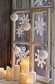 Fenster mit winterlichen Papiersternen dekoriert, davor weisse, brennende Stumpenkerzen