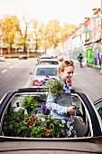 Urban Gardening: Junge Frau mit Grün-und Gemüsepflanzen in Cabrio