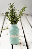 Flowering rosemary sprigs in vase with lace trim