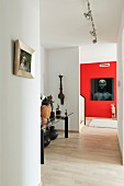 Modern hallway with object d'art on table and portrait of woman on red-painted wall