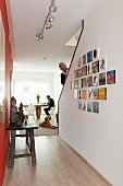 Rustic wooden table opposite gallery of pictures on wall of staircase; man walking up stairs and man sitting at dining table next to window