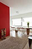 Pale grey Berber rug on wooden floor, wooden sculptures against red wall and seating area with white, classic chairs in seating area