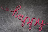 Wire covered in pink wool bent to spell 'happy'