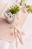Blühende Kirschbaumzweige in Vase auf rosa Decke und Federn