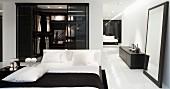 Doppelbett mit weisser Bettwäsche vor Ankleide, seitlich Standspiegel neben schwarzem Lowboard vor Wand
