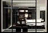 Blick durch Glaswand ins Schlafzimmer, schwarze Polsterhocker gegenüber Bett mit weisser Bettwäsche und Ankleide