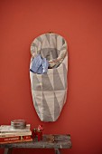 Handmade laundry bag with geometric pattern hung on red wall