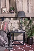 Vintage table lamp on metal side table next to vase of fern leaves against wooden wall