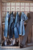 Jeans hanging from wall hooks in rustic interior