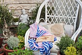 Potted herbs, Buddha statue and white orchids next to white wicker chair in garden