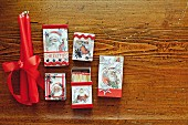 Matchboxes decorated with festive motifs and red candles tied with ribbon on wooden surface