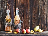 Swing-top bottles of apple juice with autumnal decorations