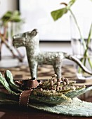 Bowl of twigs and dog ornament on table