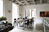 Dining table on castors with dark chairs opposite landing balustrade on open-plan gallery below concrete coffered ceiling