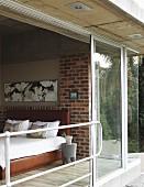 Blick von Aussen durch offene Schiebetür ins Schlafzimmer, Doppelbett mit lederbezogenem Kopfteil und Rahmen, davor ein Bubu Hocker